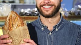 Cropped close up f a bearded man smiling holding a loaf of fresh bread. Cropped close up shot of a happy bearded man smiling cheerfully holding loaf of delicious stock footage