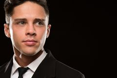 Fierce bodyguard in a black suit. Cropped close up of a handsome young man in a classy suit looking away thoughtfully black background copyspace royalty free stock images