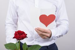 Cropped close up photo of cheerful handsome smiling sincere falling in love guy opening his heart to beloved lady reading poem. Holding card post card in hands stock photo