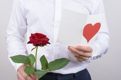 Cropped close up photo of cheerful handsome smiling sincere falling in love guy opening his heart to beloved lady reading poem. Holding card post card in hands stock photography