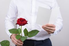 Cropped close up photo of cheerful handsome smiling sincere falling in love guy opening his heart to beloved lady reading poem. Holding card post card in hands royalty free stock photo