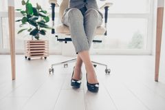 Cropped close up photo of healthy beautiful elegant woman`s legs. Wearing high-heeled shiny black shoes, the woman is sitting in office at the table on modern stock photography
