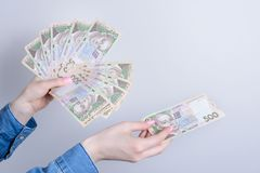 Cropped close up photo of lady`s hands holding pile stack of money gicing to copy space  grey background stock photos