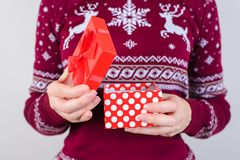 Cropped close up photo portrait of hands holding beautiful little with tied bow dotted box in hands looking aside isolated on stock photos