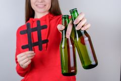 Cropped close up photo portrait of nice glad positive cheerful person holding two green glass bottles in hand giving you them. Gray background stock photo