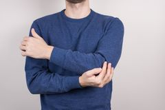 Cropped close-up photo studio portrait of unhappy unsatisfied guy holding touching elbow isolated grey background royalty free stock photo