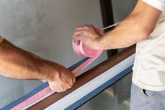 Two man using vapor barrier type and putting it on window frame. Cropped close up photo of two adult workman holding roll with special glue tape in hands and stock image