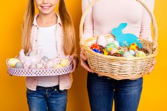 Cropped close up photo of whisker wooden baskets full of colored. Eggs cookies sweets festive figures in mother`s and small cute daughter`s hands isolated on Stock Photo