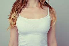 Cropped close up photo of woman`s breast in white t-shirt; she h royalty free stock photos