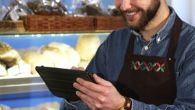 Cropped close up of a male baker using digital tablet working at the bakery royalty free stock image