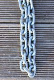 A Cropped Closeup Image Of A Linked Chain. Metal Chain Over Wooden Background. Abstract Textures Background royalty free stock photography