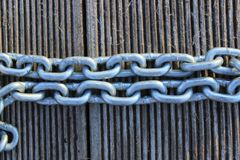 A Cropped Closeup Image Of A Linked Chain. Metal Chain Over Wooden Background.