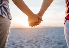 Loving lesbian couple holding hands on a beach at sunset. Cropped closeup of a lesbian couple holding hands while standing on a sandy beach watching the sunset stock image