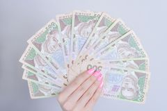 Cropped closeup photo of lady`s hands showing holding pack og ukrainian money demonstrating wealth  grey background royalty free stock photography