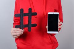 Cropped closeup photo of people person holding demonstrating showing black crossed hashtag in hand and white smart phone isolated royalty free stock photo