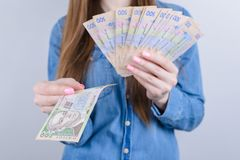 Cropped closeup photo of rich wealthy lady businesswoman holding pile stack of money in hands  grey background royalty free stock photo