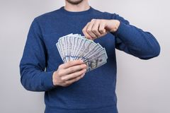 Cropped closeup studio photo of confident human showing lot of money in palms wearing sweater pullover jumper isolated grey. Background royalty free stock images