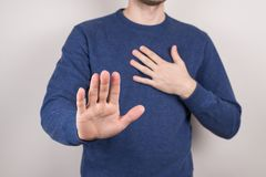 Cropped closeup studio photo portrait of unhappy sad upset guy making holding hand in front of camera on chest isolated grey royalty free stock photo