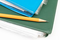 Cropped colorful folders with documents and bills and a yellow pencil on white table stock image