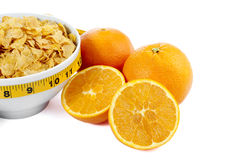 Cropped corn flakes bowl and orange fruit Stock Images