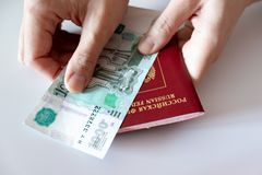Cropped female hands holding russian international passport and paper money, rubles stock image