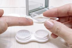 Cropped female hands taking contact lenses out of a container royalty free stock image
