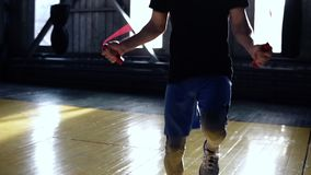 Cropped footage of a male boxer in blue shorts and leggings exercising in old style gym. Close up of man training with stock footage