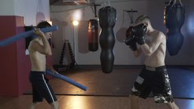Cropped frame, the athlete prepares for battle. The coach works with the boxer speed and accuracy of impact. Boxer. Training, boxing gloves, boxing pears. The stock footage