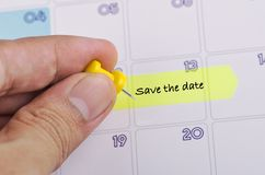 Free Cropped Hand And Yellow Sticky Paper With Word SAVE THE DATE On Calendar Royalty Free Stock Photos - 144798598