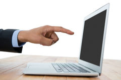 Cropped hand of businessman pointing on laptop. At table against white background Stock Photography