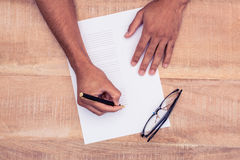 Cropped hand of businessman writing on paper by eye glasses at desk Royalty Free Stock Photography