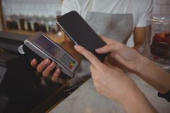 Cropped hand of customer making contactless payment with waiter holding credit card reader. In cafe Royalty Free Stock Photos