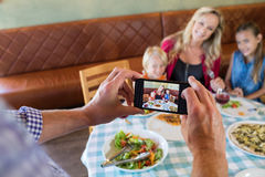 Cropped hand of father photographing family at restaurant. Cropped hand of father photographing family through smart phone at restaurant stock images