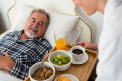Cropped hand of female doctor serving food to senior patient relaxing on bed. In nursing home Stock Images