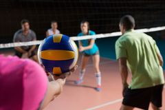 Cropped hand of player with teammates holding volleyball. Cropped hand of female player with teammates holding volleyball at court Royalty Free Stock Images