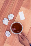 Cropped hand holding coffee cup by paper balls on desk Royalty Free Stock Photos