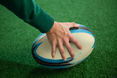 Cropped hand holding rugby ball. On playing field stock photo