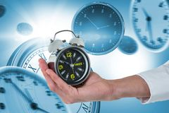 Composite image of cropped hand of male executive holding alarm clock royalty free stock image