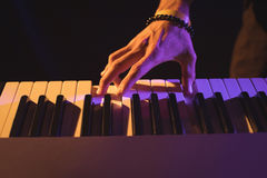 Cropped hand of male musician playing piano. In nightclub Stock Images