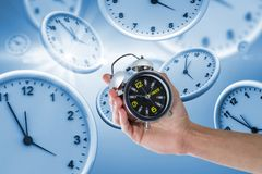 Composite image of cropped hand of man holding alarm clock royalty free stock image