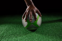 Cropped hand of person on rugby ball. Against black background stock photos