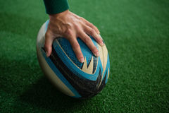 Cropped hand of person with rugby ball. On field royalty free stock images