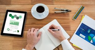 Cropped hand of person writing on diary by graphs in digital tablet at table in office. Digital composite of Cropped hand of person writing on diary by graphs in Royalty Free Stock Images