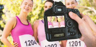 Composite image of cropped hand of photographer holding camera. Cropped hand of photographer holding camera against portrait of young athlete women posing Royalty Free Stock Photos