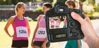 Composite image of cropped hand of photographer holding camera. Cropped hand of photographer holding camera against young female athletes interacting with each Stock Images