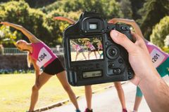 Composite image of cropped hand of photographer holding camera. Cropped hand of photographer holding camera  against young female athletes warming up in park Royalty Free Stock Photography