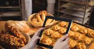 Cropped hand photographing breads in tray on table through digital tablet at bakery. Digital composite of Cropped hand photographing breads in tray on table Royalty Free Stock Images