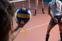 Cropped hand of player holding volleyball by female teammate. At court royalty free stock photo