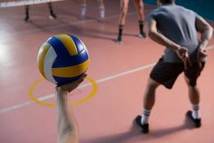 Cropped hand of player holding volleyball by teammate. At court stock images