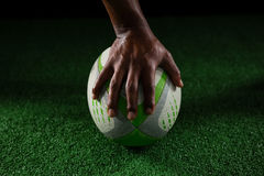 Cropped hand of sportsperson on rugby ball. Against black background royalty free stock photos
